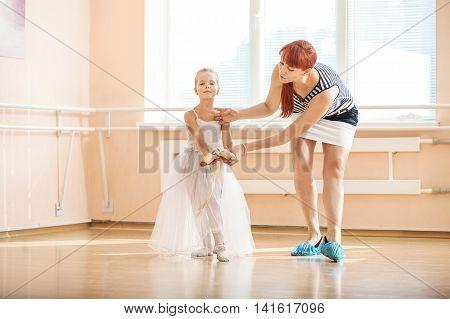 Ballet teacher adjusting position of young ballerinas at barre