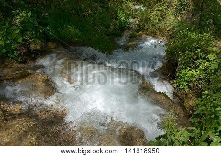 Water of fast mountain river flowing down the mountain creating cascades