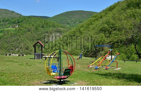 Children playground with merry-go-round seesaws and swings in lush mountain landscape in springtime
