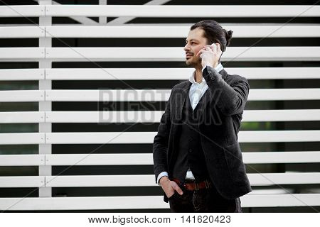 Young handsome male holding mobile phone, making a call, talking on the phone. Man in suit using his smartphone outside.