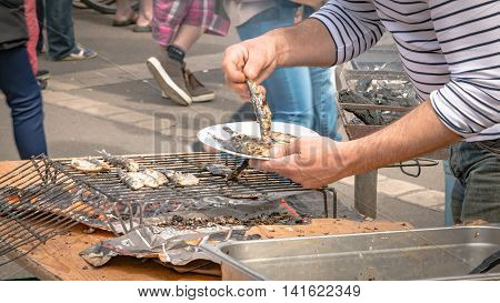 Brétignolles sur Mer France - may 5 2016 : grilled sardine seller in a market