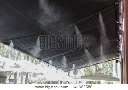 Awning sprinklers splashing vaporized water at terrace bar in order to cool the hot summer temperature in Spain
