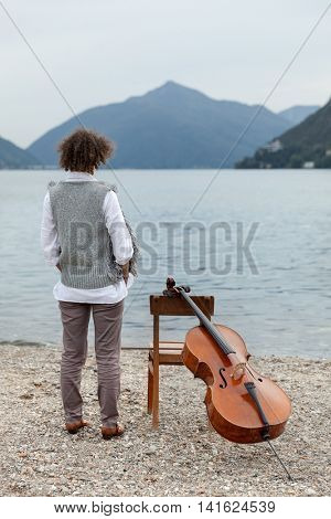 girl with the cello at the seaside, rear view