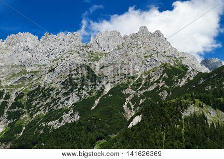 Mountain range high mountains peaks bright blue sky with clouds. Alps Austria