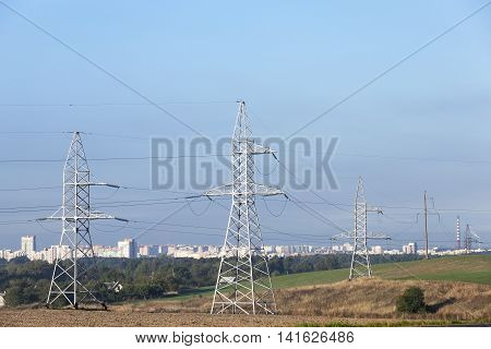 photographed electric poles located in the field during the day against the blue sky, industrial buildings