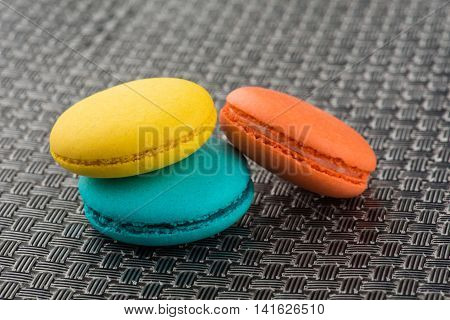 colorful macaroons on a gray metallic surface