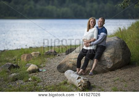 Young loving couple stands leaning on a rock by the river. Honeymoon.