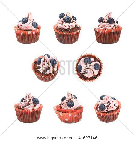 Single chocolate muffin coated with the pink cream frosting and fresh bilberries, composition isolated over the white background, set of eight different foreshortenings