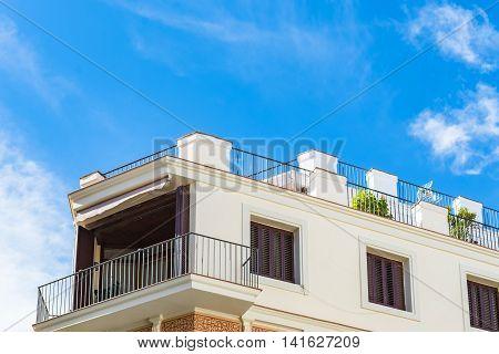 Top Corner Of Apartment Building Under Blue Sky