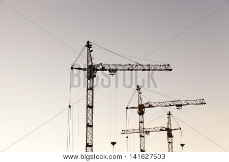 photographed close-up construction cranes during construction of a new multi-storey residential building