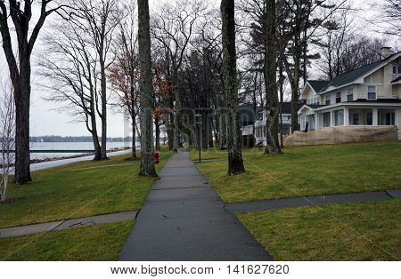 The sidewalk along Beach Drive, in Wequetonsing, Michigan, is shaded by tall trees.
