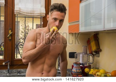 Young sexy athletic shirtless man eating apple in kitchen, choosing a healty lifestyle