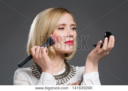 Beautiful middle aged blond woman applying blush over grey background. Copy space.