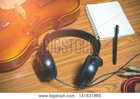 Violin phone notebook on wood background.Top view in music hipster tone.