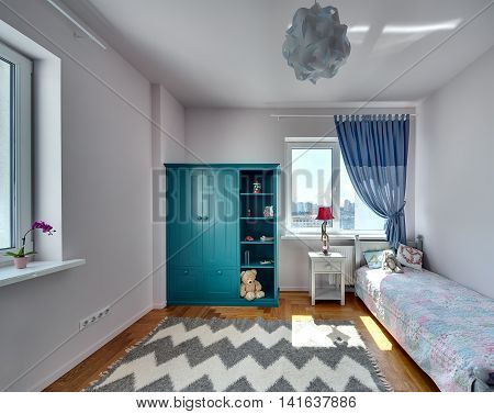 Room for kid with light walls and a parquet with carpet on the floor. There is a bed with colorful veil and pillows and a toy, turquoise bookcase with toys and books, nightstand with a lamp.