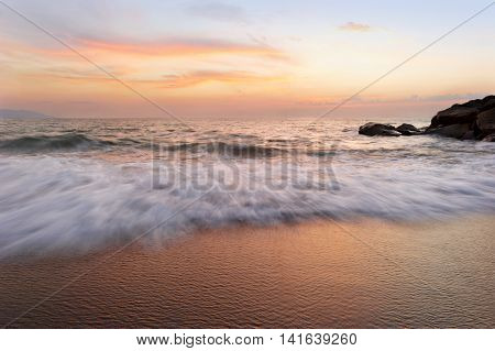 Ocean sunset is a soft pastel colored beach setting with a detailed cloudscape and a gentle wave rolling to shore.