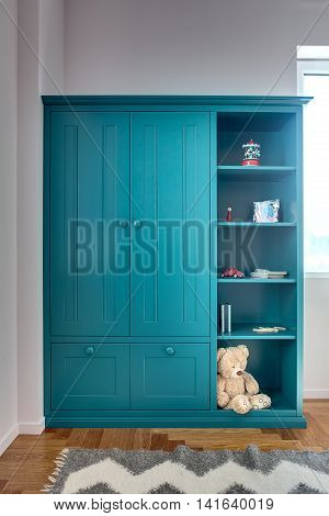 Kid's turquoise bookcase with toys, books, notebooks, pencils and a big teddy bear. On the floor there is a parquet with a gray carpet. Walls are white. Indoors. Vertical.