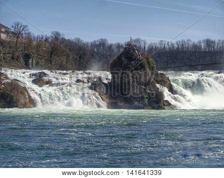 Neuhausen am Rheinfall, Switzerland - 9 April 2015: the Rhine Falls. The Rhine Falls (German: Rheinfall) is the largest plain waterfall in Europe located on the Rhine river in Switzerland.
