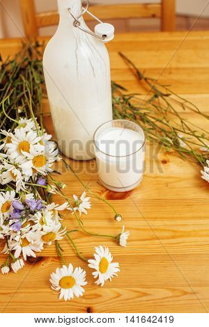 Simply stylish wooden kitchen with bottle of milk and glass on table, summer flowers camomile, healthy food moring concept close up