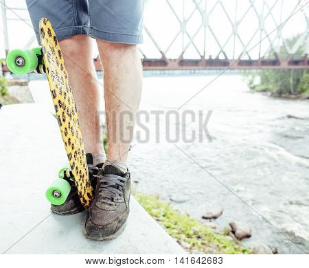 young handsome real hipsrter guy bearded staying under the bridge extreeme with leopard skateboard, lifestyle people concept close up