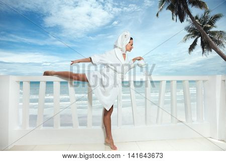 Woman with coffee in hotel terrace over sea view