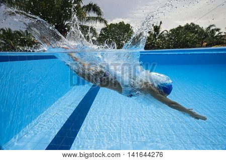 Portrait of a female swimmer, that jumping and diving into swimming pool. Sporty woman.Low angle view from the swimming pool.