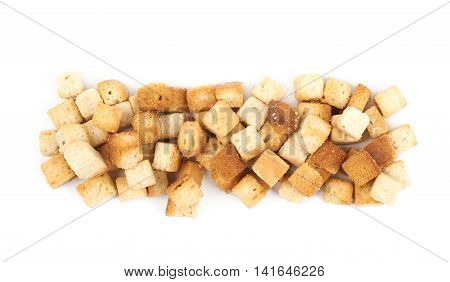 Lined up pile of garlic white bread croutons isolated over the white background