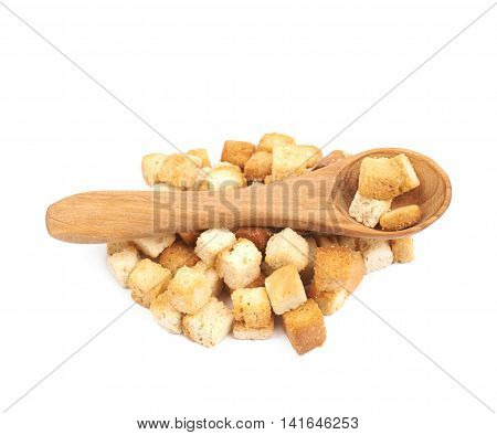 Pile of garlic white bread croutons with a wooden spoon over it, composition isolated on the white background