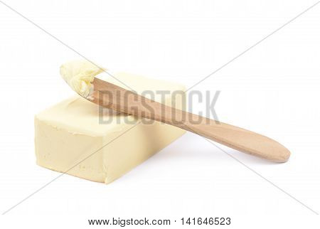 Wooden knife over a briquette piece of a butter, composition isolated over the white background