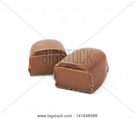Chocolate coated toffee candy sliced in two parts, composition isolated over the white background