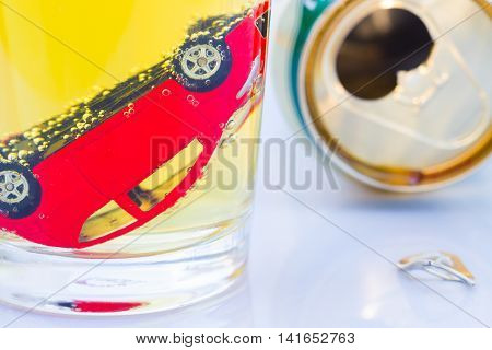 horizontal photo of red toy car in a glass of beer isolated on white background. Drunk-driving Prevention Concept.
