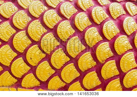 sculpture of golden dragon scale or Fish scale textures in Thai temple.