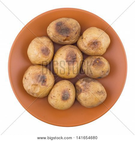 Baked potato in a brown plate isolated on white. Top view.