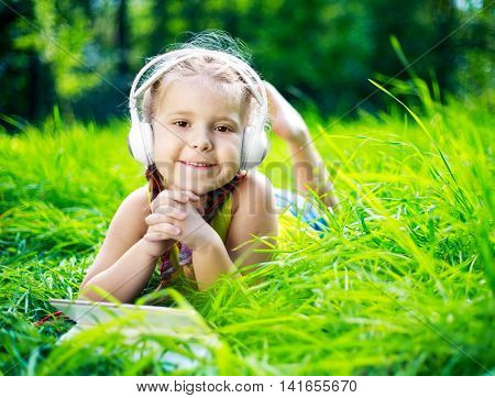 happy girl with earphones  listening to the music on a summer day