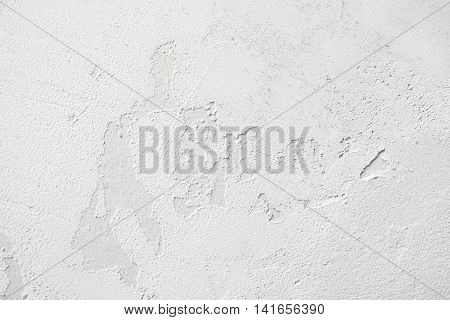 Old white stucco peeling wall background, free space. Grungy plaster backdrop