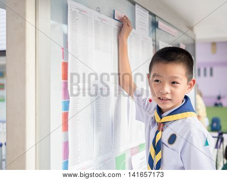Asian kid find the result announcement of exam s primary school