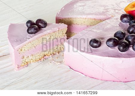 Cut piece fruit cheesecake decorated with grapes. Closeup