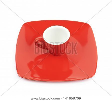Tiny red espresso ceramic cup over the square shaped plate, composition isolated over the white background
