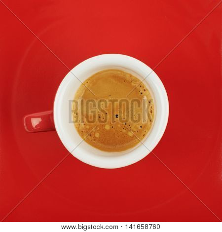 Tiny red ceramic cup filled with the espresso coffee, placed over the red surface