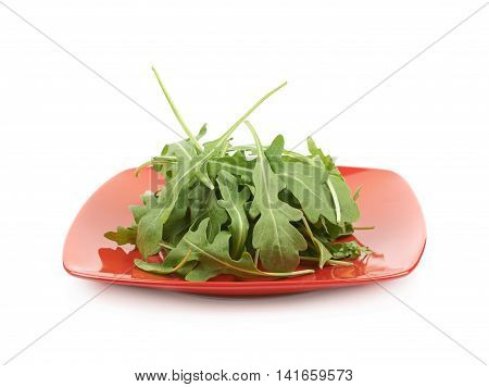 Red ceramic plate full of rocket salad leaves isolated over the white background