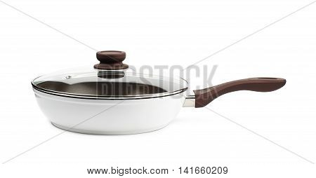 Brand new brown frying pan with a teflon coating and a glass lid over it, composition isolated over the white background