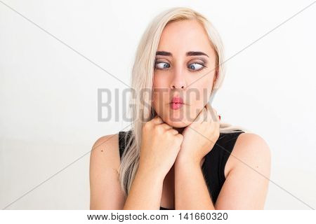 Crazy blonde woman makes squint for fun. Close-up portrait of cheerful funny blonde with strabismus, white background