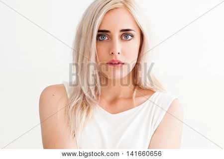 Surprised shocked blonde girl biting her lip with widely opened eyes. Amazed woman in light cloth on white background, free space