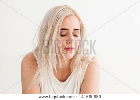 Upset woman with eyes closed. Concept of misunderstanding, loneliness, frustration, failure, loss. Attractive blonde on white background