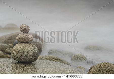 Three pebbles stacked in the foreground foggy background with free space for text Zen concept Horizontal image.