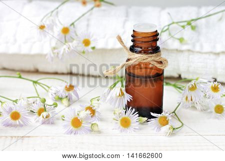 Essential oil, aroma dropper bottle decorated with twine, flowers, white bathroom terry towel.