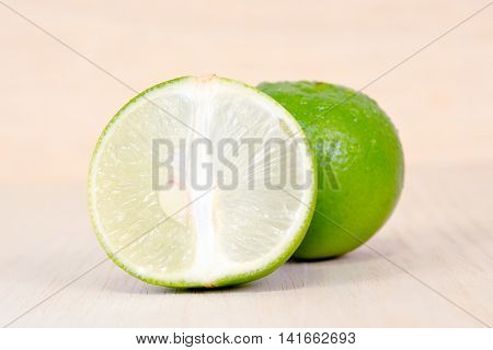 Lemon Or Lime Fruit With Half Cross Section Isolated On Wooden Board