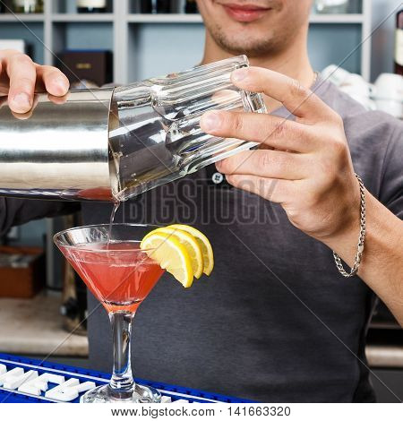 Barman's hands in bar interior mixing cosmopolitan alcohol cocktail. Professional bartender at work in bar