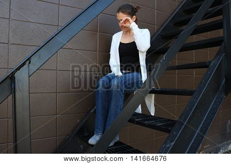 Sad Girl Sitting Alone on a Stairwell