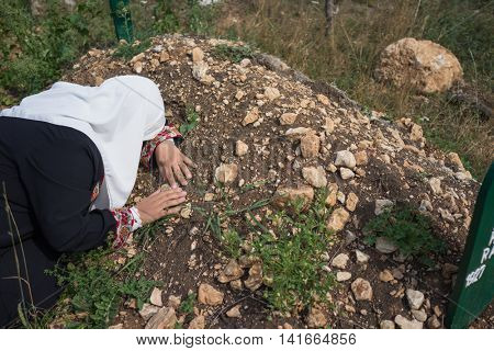 Muslim woman visiting grave in cemetery